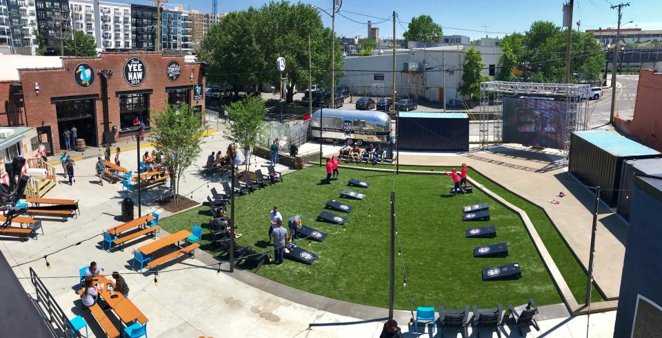 The 6th and Peabody complex showing a lawn, cornhole games, YeeHaw Brewing Co. and Ole Smoky Distillery in downtown Nashville