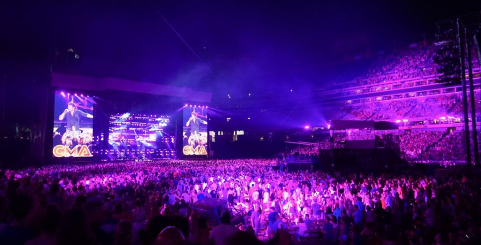 Crowd at Nissan Stadium in neon purple lights at CMA Fest