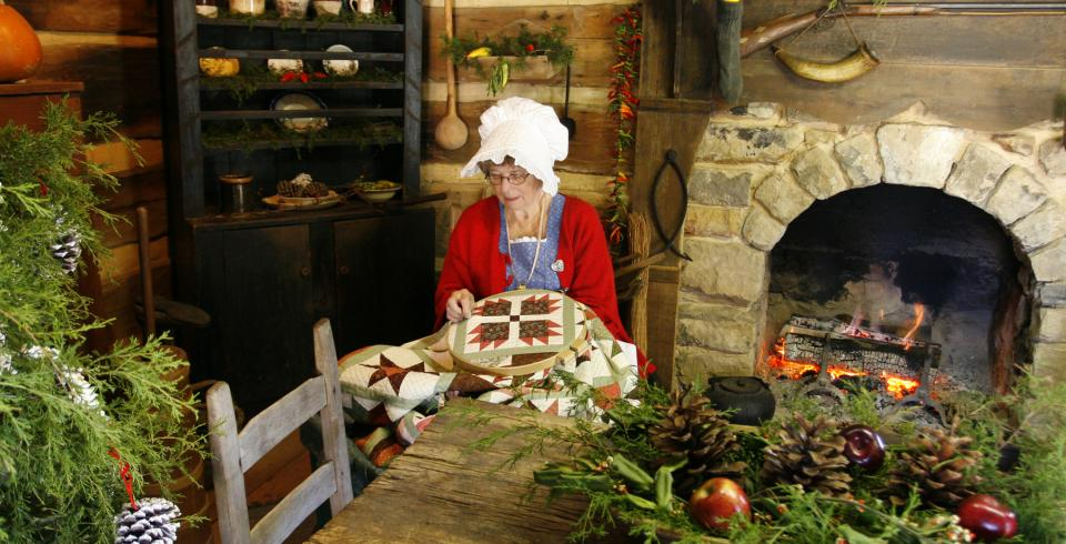 A pioneer woman sits at a decorated table at Museum of Appalachia