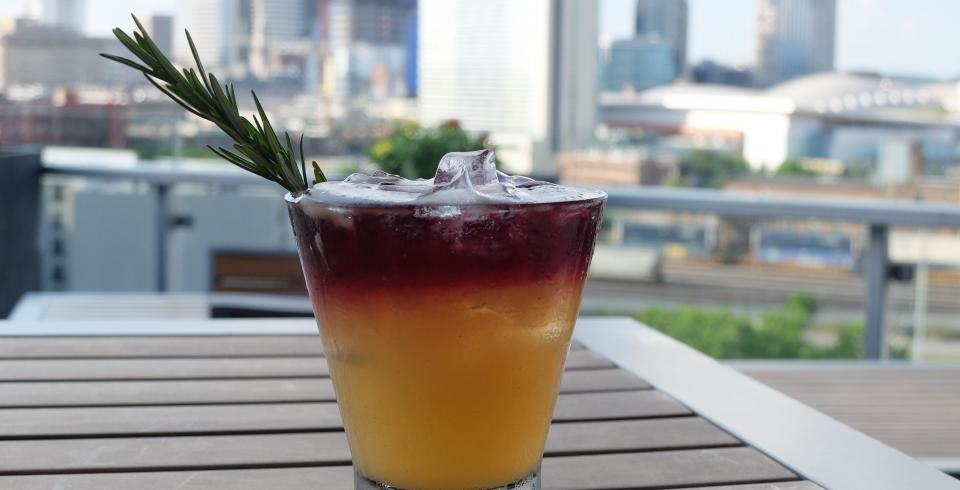 A cocktail at UP Rooftop Lounge with a Nashville skyline view