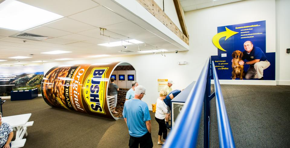 Visitors walking through the Bush's Beans interactive exhibits, like the bean can filled with videos and more information.
