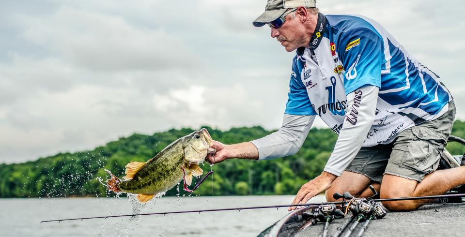 A fisherman pulls out a bass from Chickamauga Lake in Dayton, TN