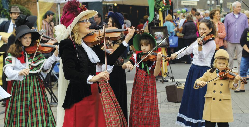 Fiddlers in Victorian costume performing at Dickens of a Christmas in Franklin