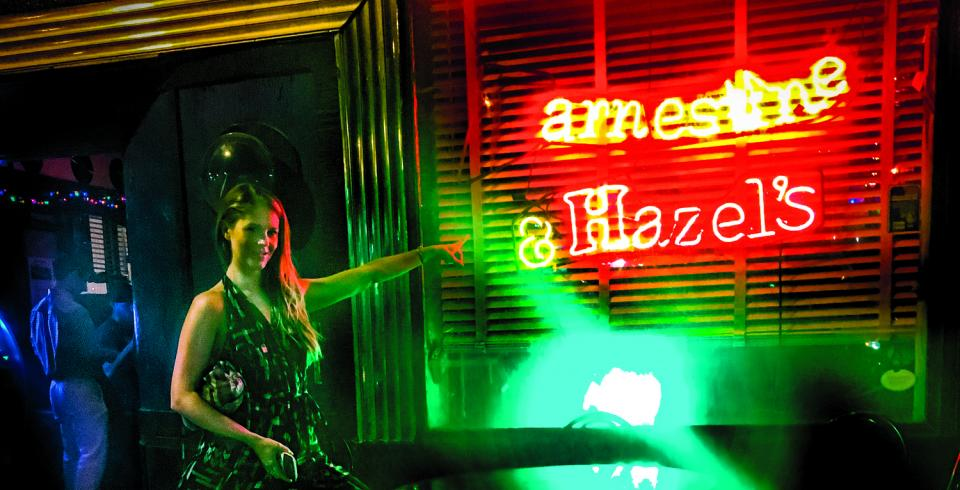 A girl points to the Earnestine and Hazel's sign in Memphis, TN