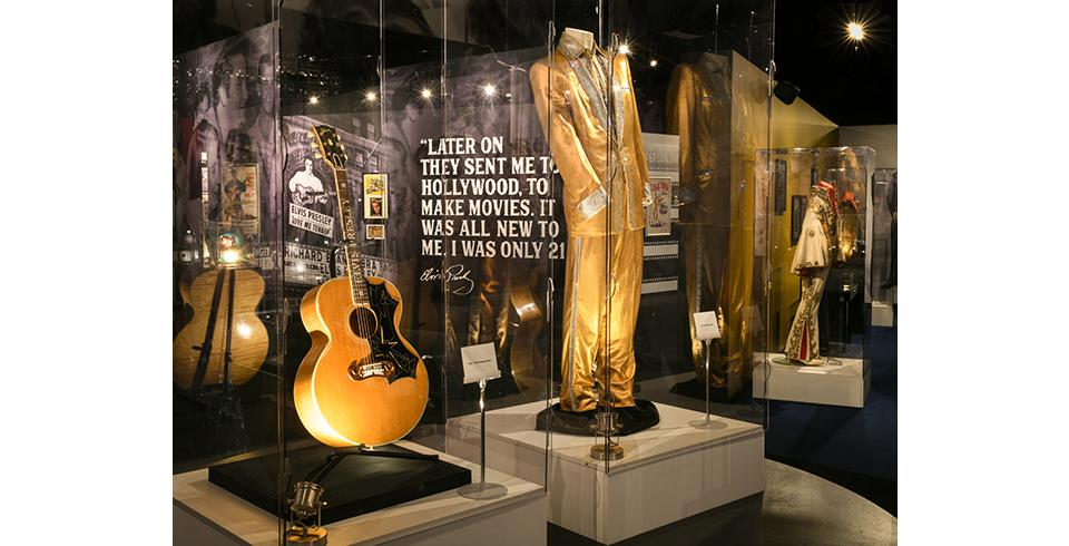 An acoustic guitar and Elvis' gold suit on display at Elvis Presley's Memphis.