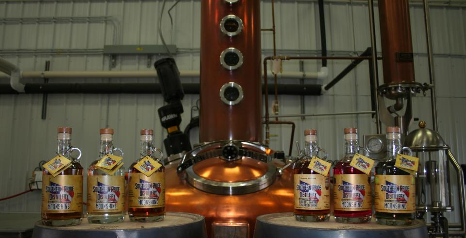 Distilled spirits with distiller in the background from Southern Pride Distillery in Fayetteville, Tennessee