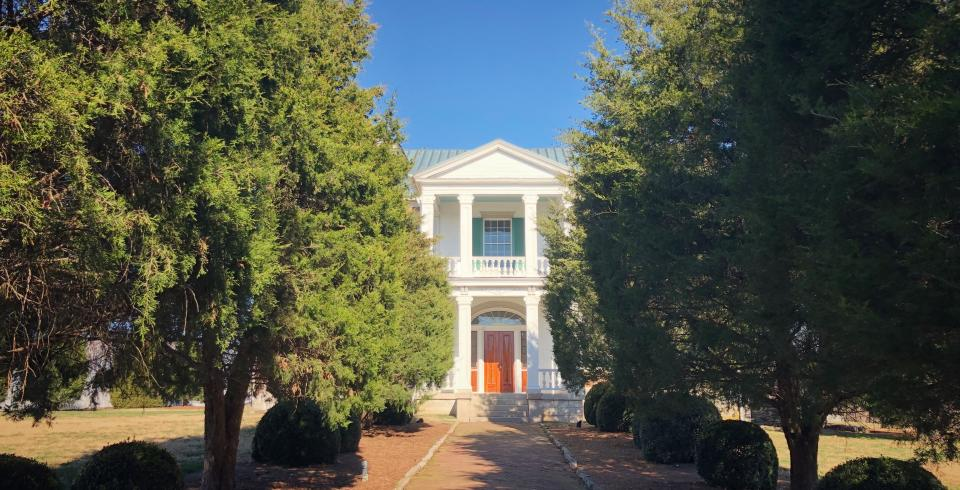 The exterior and tree-lined walkway of Carnton in Franklin TN