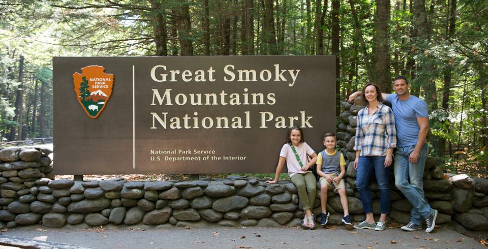 A family of four poses in front of the Great Smoky Mountains National Park sign.