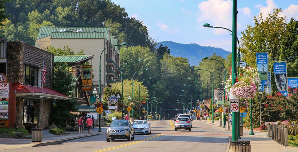 Cars driving through downtown Gatlinburg, TN on a sunny day.