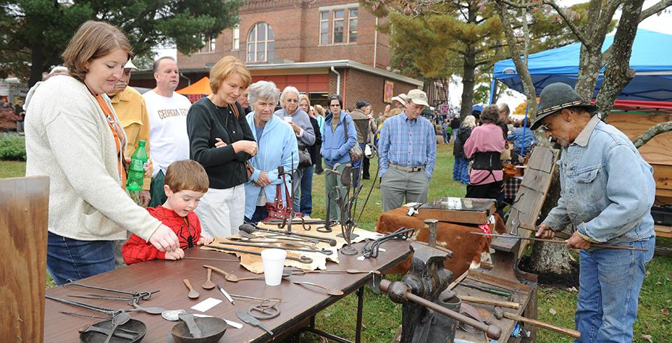 A group watches a blacksmithing demonstration.