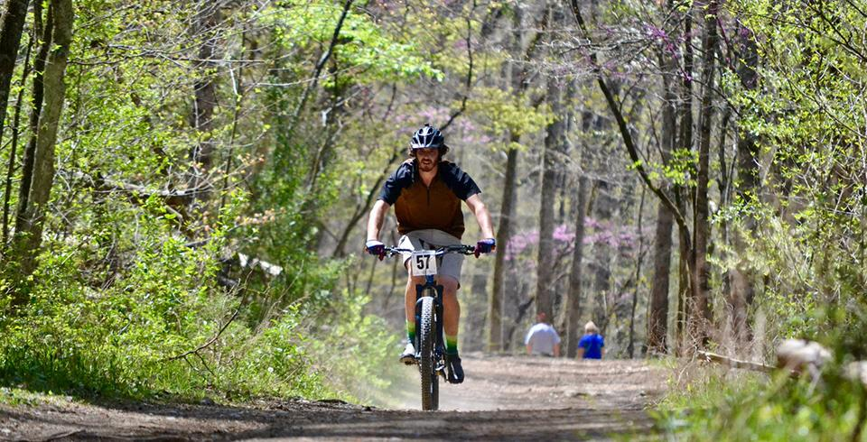 A man bikes on natural trails at Panther Creek State Park.
