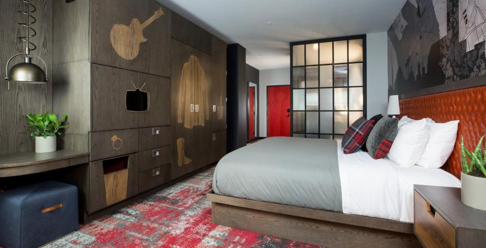 A bedroom with a king sized bed and guitar mural in the Bobby Hotel