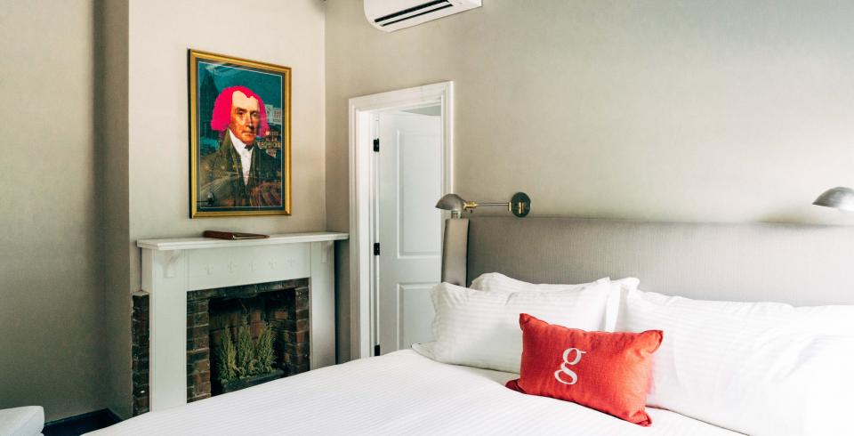 A light, airy bedroom with white linens, a fireplace and a modern piece of art at the Germantown Inn