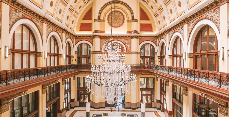 The historic lobby with a chandelier and leather upholstered chairs and couchesthat is still reminiscent of a train station at the Union Station Hotel.