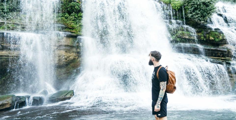 A hiker stands at the base of the waterfall at Rock Island State Park in TN
