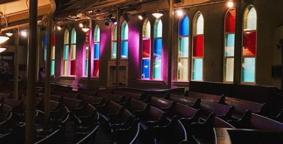 Inside the Ryman Auditorium, the stained glass windows reflecting light onto the pews.