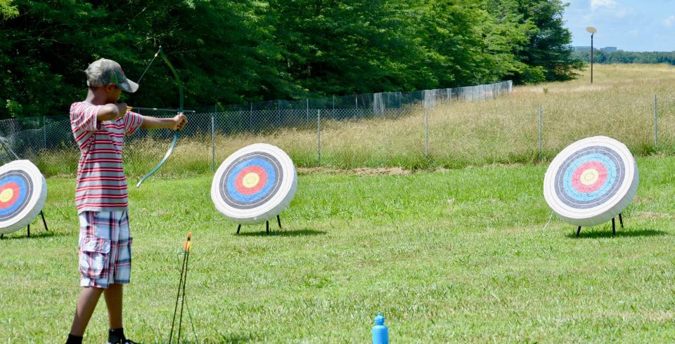 A kid in an archer's stance in front of a bullseye at Shelby Farms Park in Memphis