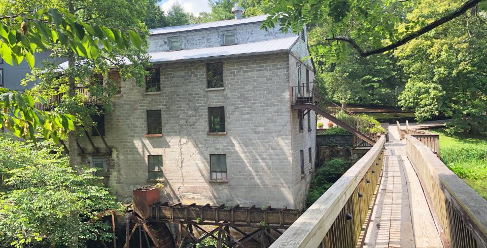 A wooden bridge leads to the historic mill at Evins Mill in Smithville