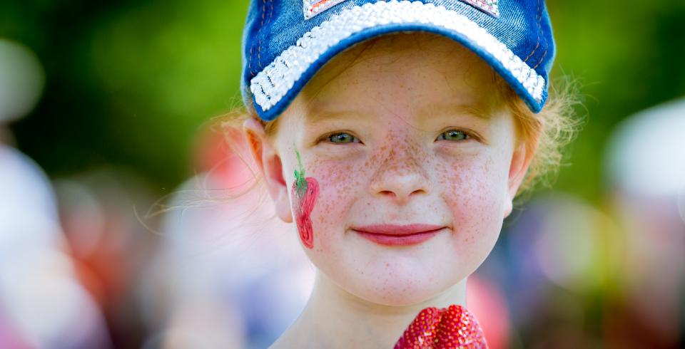 Girl holds strawberry at Middle TN Strawberry Festival in Portland TN