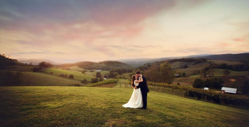 A sunset photo of a newly married couple on the hills of Villa Nove Vineyards with the Appalachian Mountains in the background.