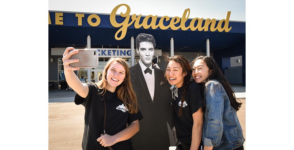 Three girls pose with an Elvis cutout at Elvis Presley's Memphis.