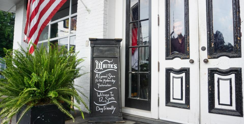 The outside of Whites Mercantile with a chalkboard, American flag and ferns