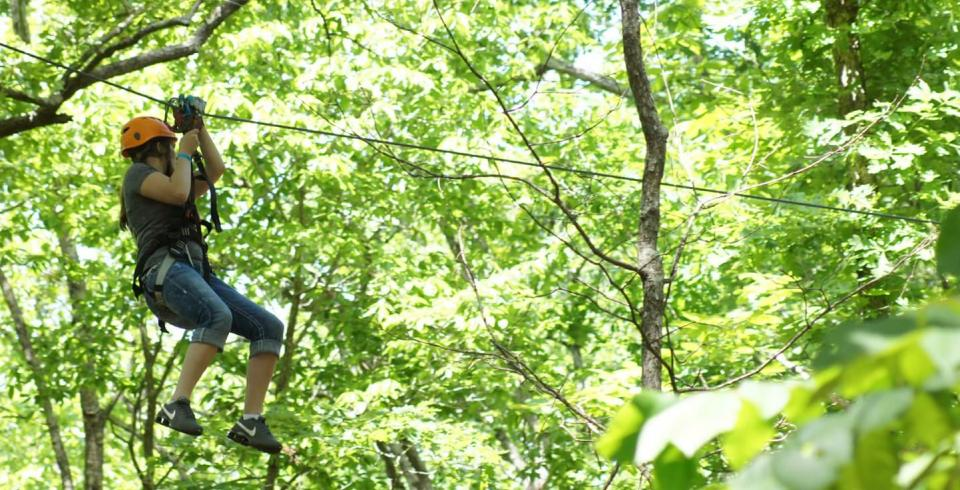 A girl ziplines through the green trees at the Canopy Challenge Course at Fall Creek Falls State Park