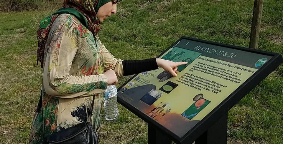 A woman reads the informational sign at Pinson Mounds State Archaeological Park
