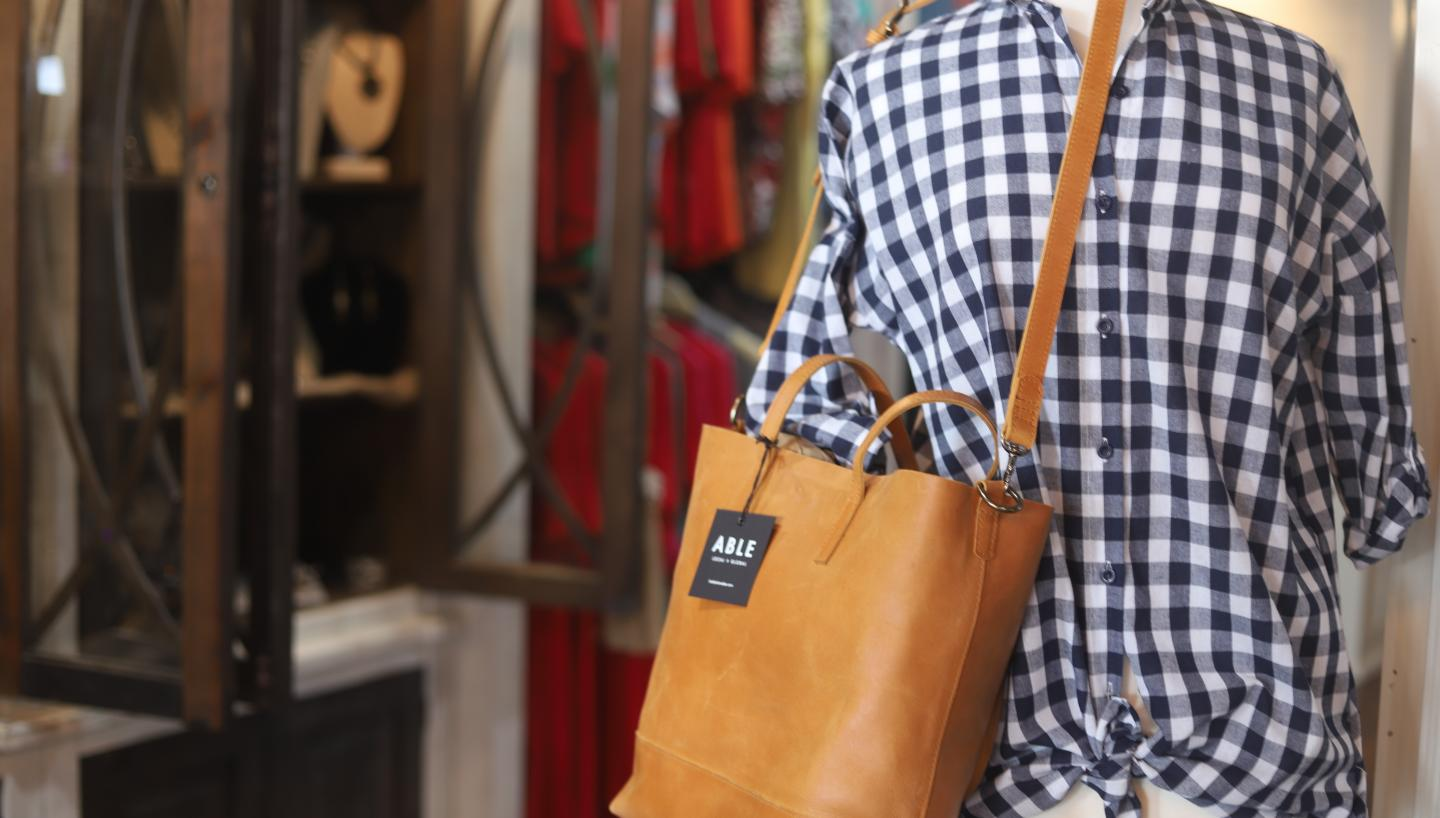 ABLE leather goods and a gingham shirt on display at Main Boutique.