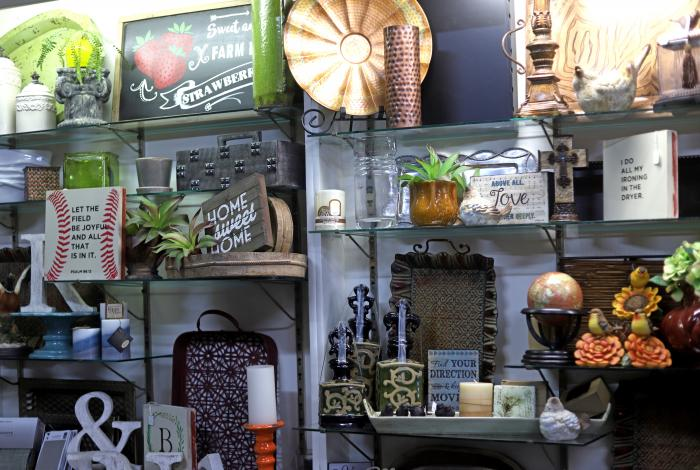 Home decor pieces, serving trays and wood signs on display at Creative Accents.