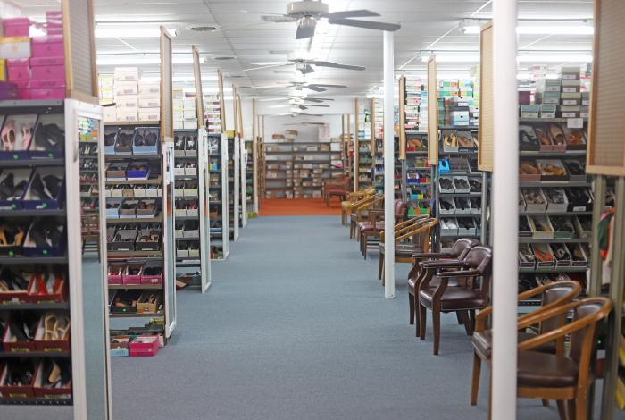 A long hallway filled with women's styles of shoes.