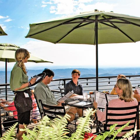 Guests at Cafe 7 with a mountain view, dining on the patio.