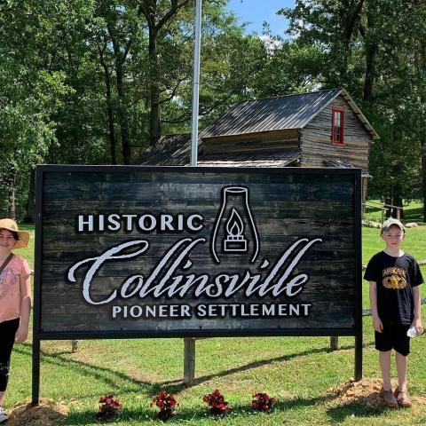 children by a Historic Collinsville entry sign