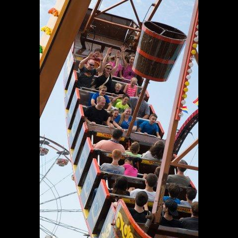 People riding a swinging fair ride.