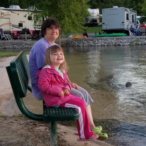 Family sitting at Lillydale beach with campground in the back