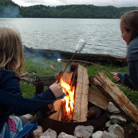 Two children roasting marshmallows by the lakeside