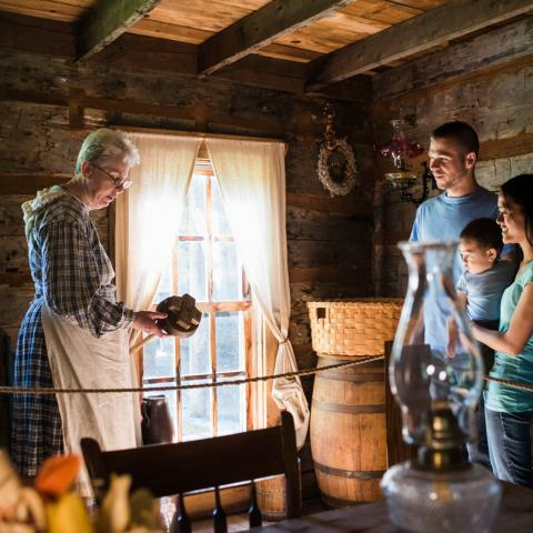 A docent explains a kitchen tool to a family at Historic Collinsville Pioneer Settlement.