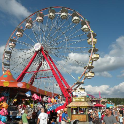 Picture is of a large ferris wheel with a blue sky background. Lots of people in the foreground.