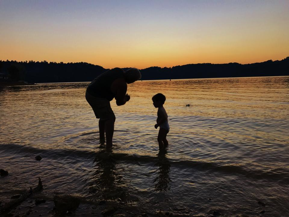 Grandfather and child on shoreline