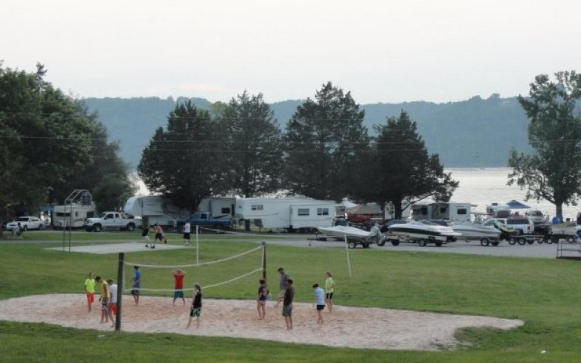 people playing volleyball with campground and lake in background