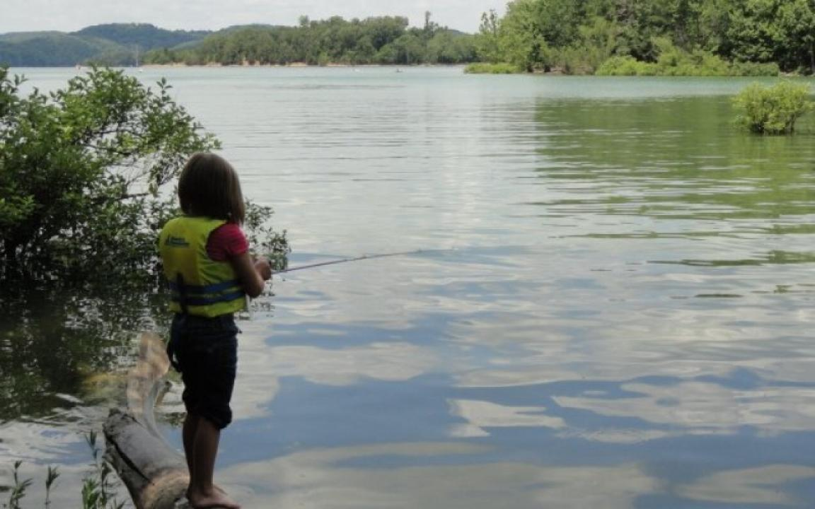 Child in life jacket fishing